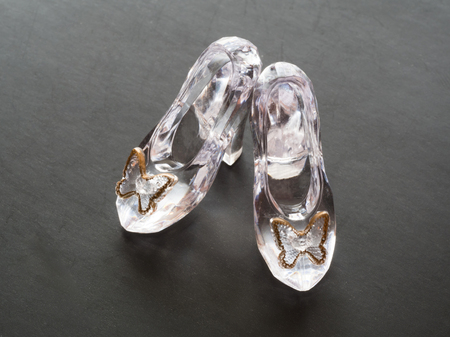 Clear glass pair of shoes for doll isolated on black background