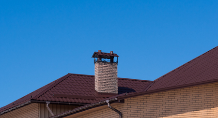 Modern chimney under clear blue sky. Rain gutter and snow guard on the roof Stock Photo