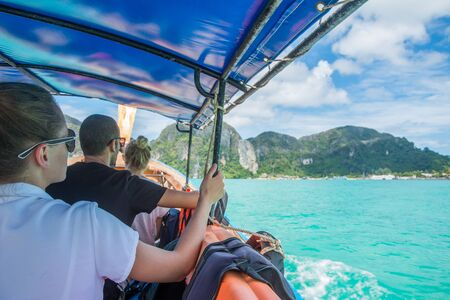 PHI PHI ISLAND, THAILAND - MARCH 31, 2017: Tourists make journey on long-tail boat to the island in the daytime