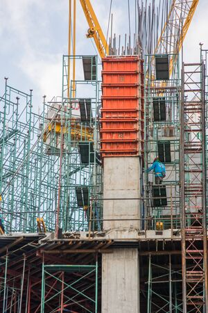 BANGKOK, THAILAND - APRIL 1, 2017: Builders on the building site of modern building made of armature and concrete. Workers on the scaffolding