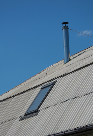Slate roof with metallic chimney and skylight under blue sky