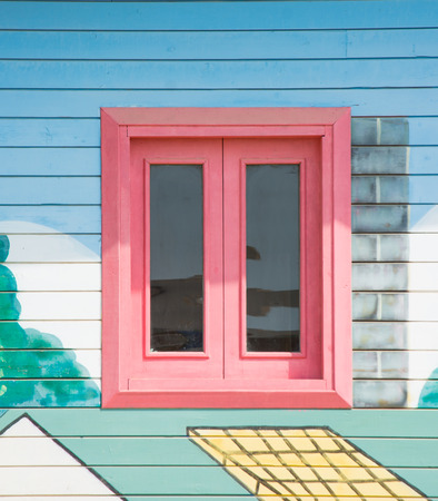A wooden rectangular window of pink color at the playground