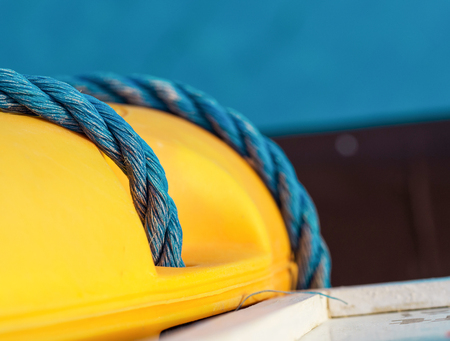 Blue twisted rope on the yellow lifebuoy, macro, shallow dept of field