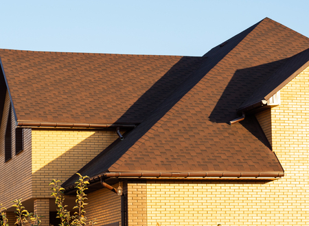 Modern multilevel rooftop of the brick mansion with rain gutters. Blue sky background
