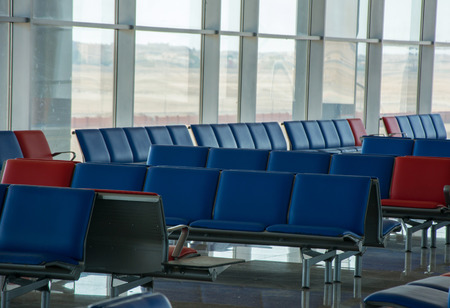 Empty airport terminal waiting area with chairs in red-blue colors, travel and vacation concept Archivio Fotografico