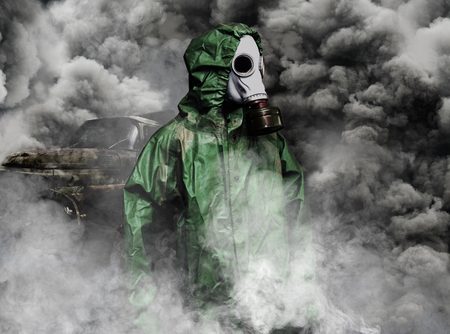 Man in gas mask and cloak of chemical protection in smoke of vehicles, air pollution concept