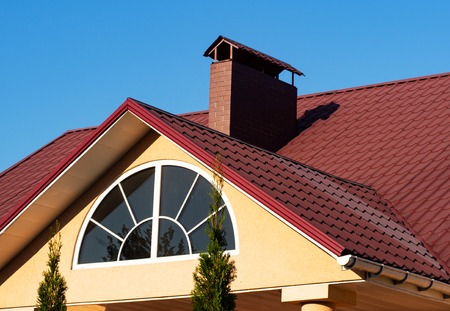 Semicircle window and brick chimney on the red metal tile roof under blue sky, house exterior