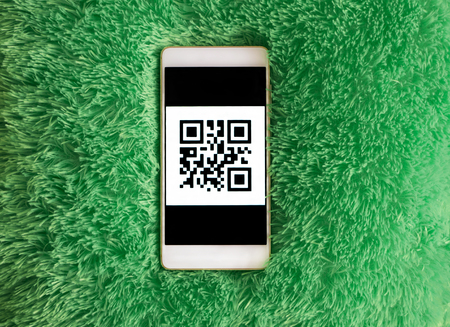 Mobile phone with qr-code on the screen. Blue-green artificial soft nap background