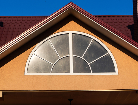 Arched window with white frame, close up, house exterior Banque d'images