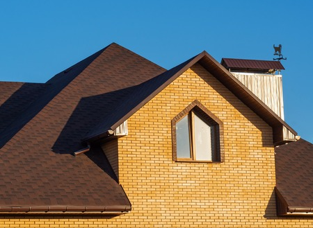 Brown multilevel roof of modern brick house with window and rain gutters Stock Photo
