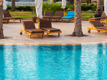 Brown empty loungers near the swimming pool with turquoise water Stock Photo