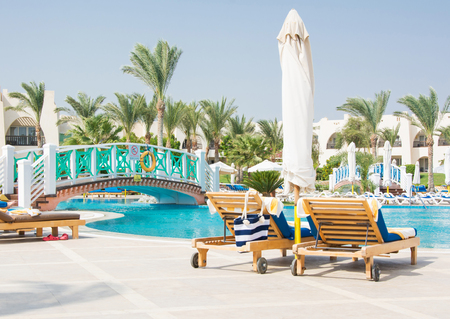 Wood chaise lounges with beach bag near the swimming pool at the hotel Stock Photo