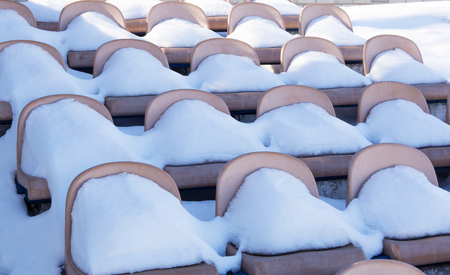 Rows of empty stadium bleachers covered with snow