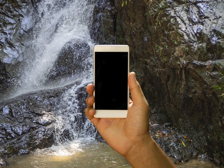 Mockup image of a mans hand holding white mobile phone with blank black screen and focused waterfall on the background Stok Fotoğraf