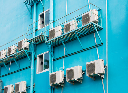 Rows of white conditioners on the turquoise wall, outdoor. Industrial ventilation