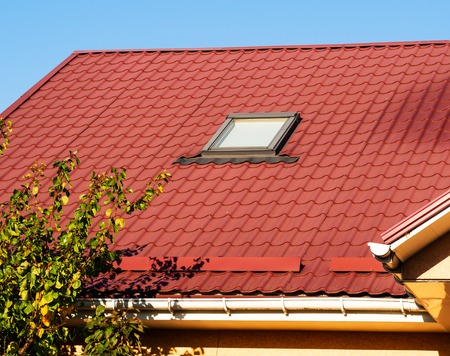 Close up of skylight and snowguards on terracotta metal tile roof