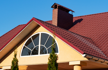 Hemicycle window and brick chimney on the red metal tile roof, house exterior