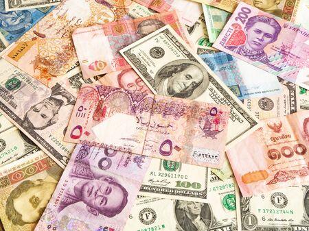Hintergrund aus Dollar, Thai Baht, Katar-Riyal, Griwna-Banknoten. Globale Währung Standard-Bild