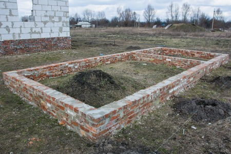 Building Brick foundation of new house construction on ground