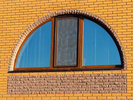 Close up semicircle wide window in brick wall Archivio Fotografico