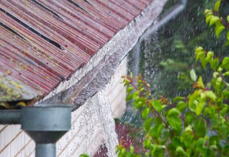 Water overflowing from damaged rain gutter during a heavy rainstorm Stok Fotoğraf