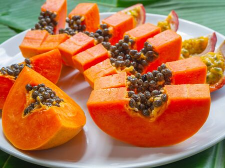 Vegetarian nutrition. Exotic and tropical fruits. Papaya pieces and passion fruit on white plate, closeup Stok Fotoğraf