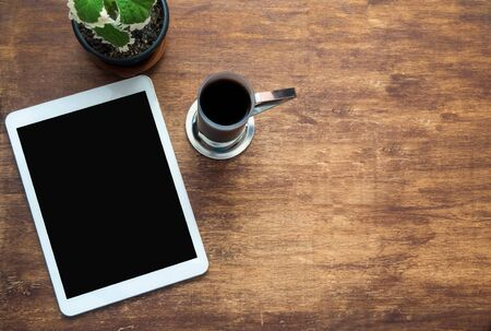 Touch tablet and cup of coffee on wooden desk. Black blank space on the screen. View from above Banque d'images - 132222002
