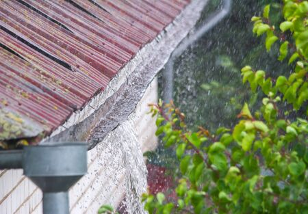 Closeup of water overflowing from old gutter during a heavy rainfall