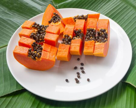 Top view of papaya pieces on plate, green banana leaves on background. Vegetarian nutrition
