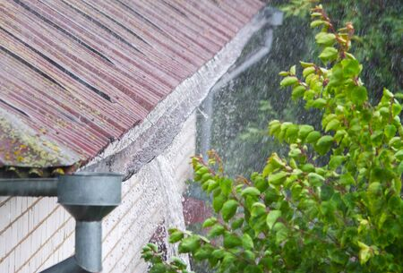 Closeup of leaking rain gutter full of water