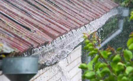 Gutter overflowing during downpour. Rain gutter needs reconstruction Stok Fotoğraf