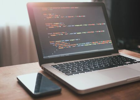 Computer code on the screen (web developing). Laptop and smartphone on the table in sunlight Stock Photo