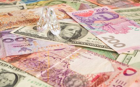Clear glass pair of shoes on different currencies. Money for love. Prostitution Stock Photo