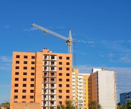 Facade of unfinished brick multistory building under construction with crane under blue sky