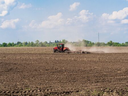 Farmer cultivating arable land before seeding. Tractor working on the farm, a modern agricultural transport,