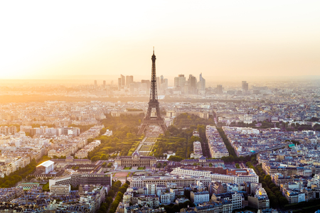 Eiffel Tower and Skyline of Paris, France with houses, streets and parks and with warm, colorful sunset light with business district La Defense in the background