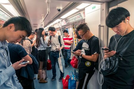 Asian People Staring at Smartphone inside Train in Shenzhen, China - April 2018