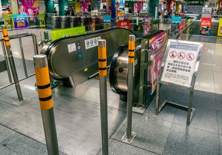 Pillars in front of escalator entrance in underground rail station of Shenzhen, China - April 2018