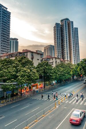 People crossing street in urban scene - Shenzhen, China - April 2018