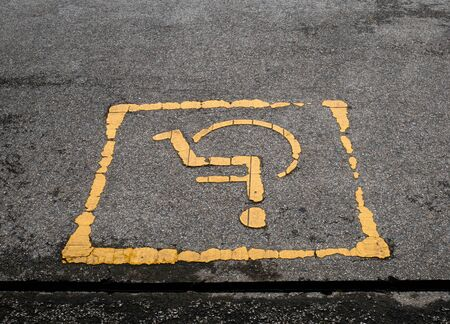 Disabled parking sign painted on the street.