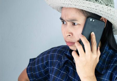 Asian young woman angry while talking on phone in vacation day, Isolated on grey background.