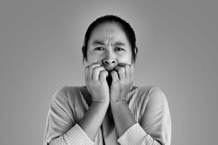 Asian woman frightened shocked what she see and holding hands near mouth, Isolated on dark background.