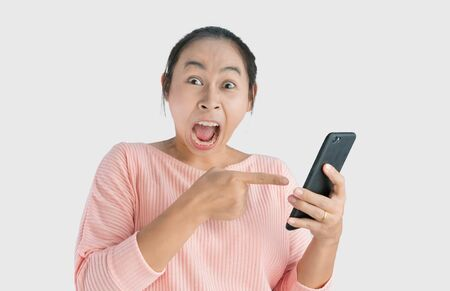 Asian woman angry and yelled what she see in the smartphone and pointing it, Isolated on white background.