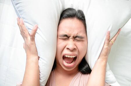 Asian young woman used pillow over her ears while alarm clock on bed in the morning.