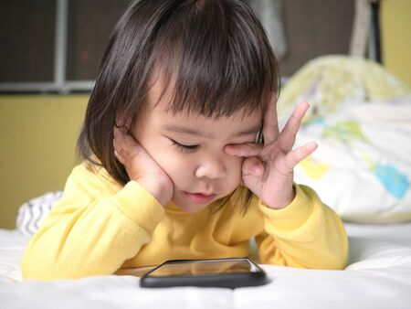 Asian little girl rubbing her eyes feel painful after watching smartphone on bed. Kid addicted to mobile phones.