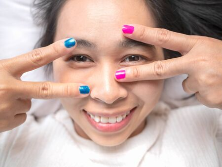 Close-up of female showing hands paint nail varnish with smiley face, self made manicure at home. 写真素材 - 133669454