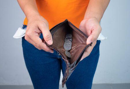 Donna disoccupata e in bancarotta che mostra poca moneta nel suo portafoglio. Concetto di recessione economica. Archivio Fotografico
