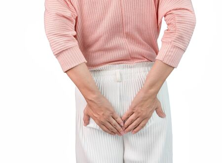 Woman suffering from hemorrhoids and hand holding her bottom. Health care concept.