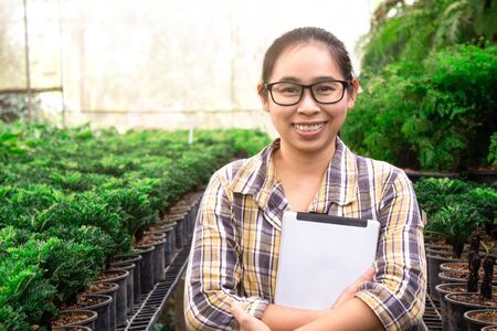 Asian gardener woman standing with tablet in seedling nursery and smile to camera. Technological and agricultural concepts.