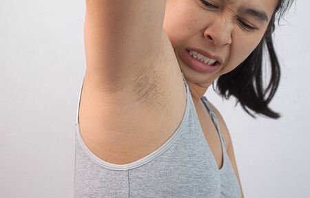 Close up of young woman showing her unshaved armpit and offensive face isolated on grey background. Concept of Health care for skin and beauty.
